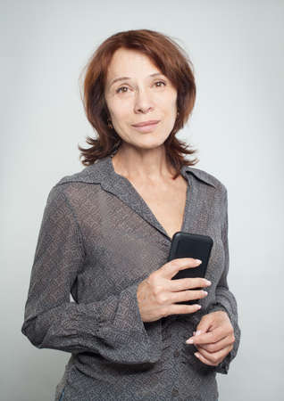 Mature woman with smartphone on white Imagens