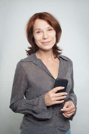 Happy mature business woman with cell phone Stockfoto