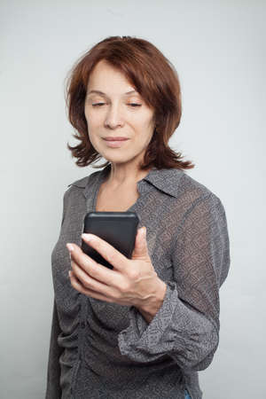 Mature woman with mobile cell phone, portrait Imagens