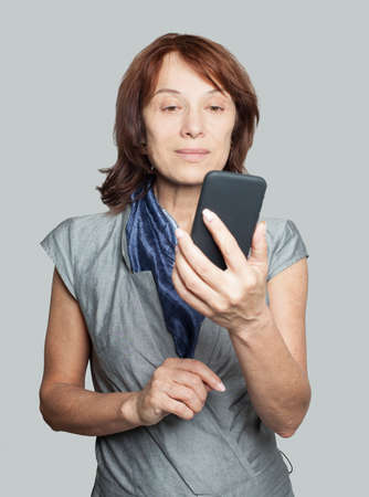Mature woman using smartphone and chatting Imagens