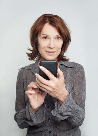 Smiling mature woman with cell phone