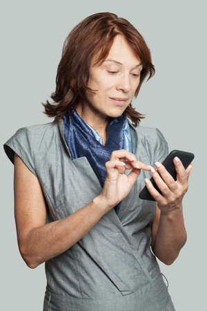 Mature woman with smartphone texting coworker. Business woman cell phone