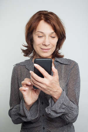 Mature woman texting on white 写真素材