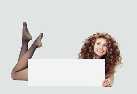 Young happy woman in black tights lying on white and showing big empty paper card banner Standard-Bild