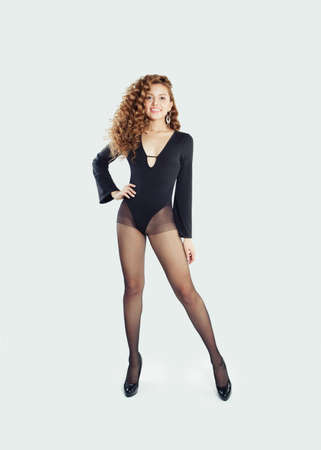 Pretty woman wearing black tights and body on white wall