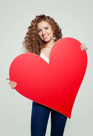 Young woman student with red empty paper heart  with copy space for advertising marketing or product placement