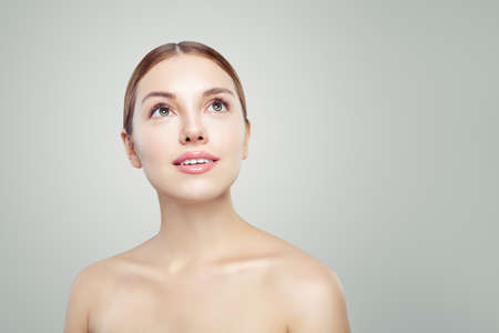 Healthy woman looking up. Young perfect model face with clear skin. Facial treatment, skincare and cosmetology concept.