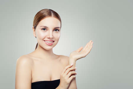 Cute gitl smiling and holding empty open hand. Facial treatment, face lifting, anti aging and skin care cosmetics concept. Stock Photo