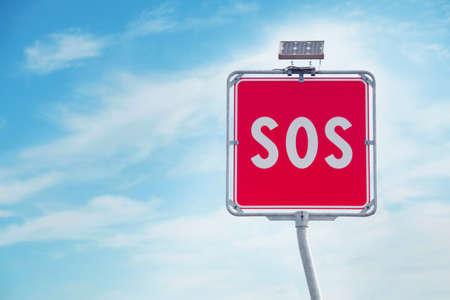 Sos sign on blue sky background. SOS sign and phone box on highway in Italy