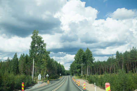 Road and forest with blue sky and clouds
