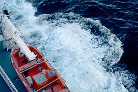 A top view on orange lifeboat on the deck of a ship sailing in the Baltic sea