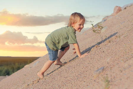 Niño subiendo a la duna de arena. Día de verano Foto de archivo