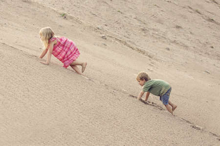 Girl and boy Climbing On The Sand dune. Summer day