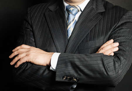 Close up of a man in a suit with his hands arms crossed