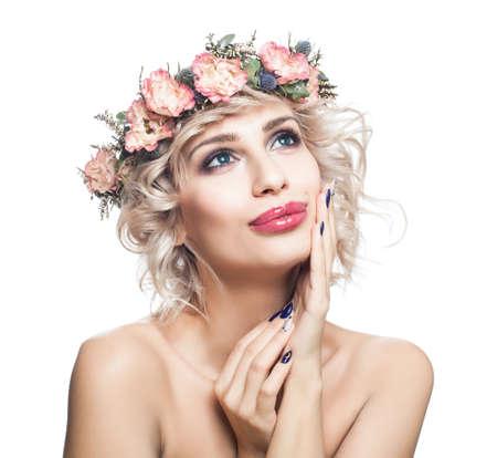 Disfrutando de mujer con pelo rizado rubio corto, maquillaje y corona de flores mirando hacia arriba aislado en blanco