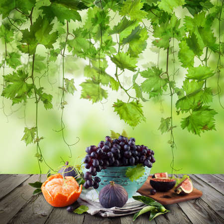Fruit on wooden table in green sunlight garden. Eco green grapes tree background Banque d'images