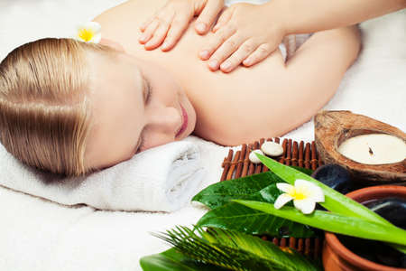 Spa massage with aromathrepy. Beautiful young woman getting spa massage. Spa concept Stock Photo