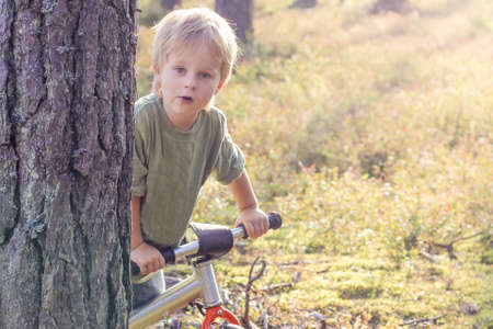 boy riding a bike in the forest. Lifstyle concept Фото со стока