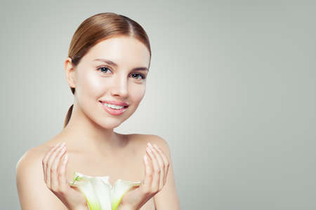 Beautiful woman face. Healthy model with clear skin and flowers. Skincare and facial treatment concept