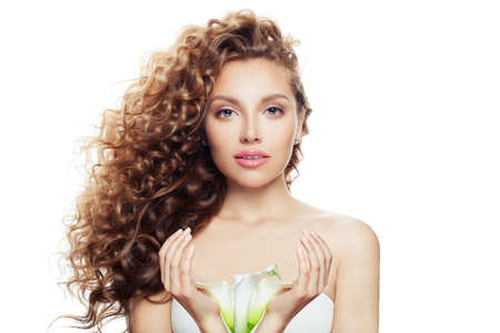 Young perfect woman with long curly hairstyle, healthy skin and lily flower in her hands isolated on white background