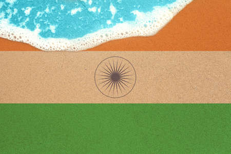 Sea wave on the sunny sandy beach with flag India. View from top on surf. Stock Photo