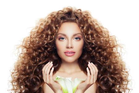 Hermosa mujer joven con pelo largo y rizado, piel clara y flor de lirio aislado en blanco Foto de archivo