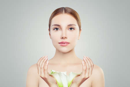 Young woman with clear skin and flowers. Skincare and facial treatment concept Foto de archivo