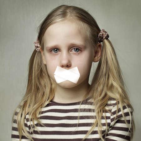 Adolescent triste avec la bouche scellée. Enfant avec des larmes - jeune fille pleurant