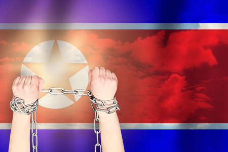 Two hands shackled a metal chain on the background of the North Korea flag. Freedom concept
