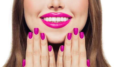 Nägel und Lippen. Frau, die ihre Wangen ihre Hände mit Manikürenägeln berührt Rosa Lippenstift und Nagellack Standard-Bild