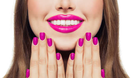 Nails and lips. Woman touching her cheeks her hands with manicure nails. Pink color lipstick and nail polish Imagens
