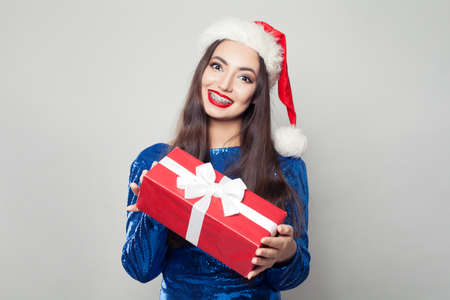 Pretty woman in braces holding Christmas or New Year gift and smiling