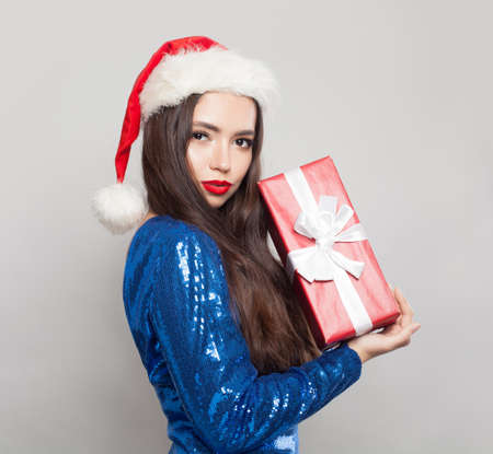 Beautiful brunette woman in Santa hat holding Christmas gift