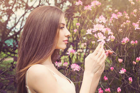 Beautiful woman face with clear skin, profile. Healthy girl sniffing flowers