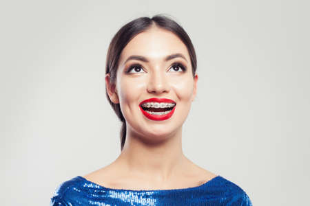 Portrait of happy beautiful woman in braces on white background. Pretty girl with braces on teeth smiling