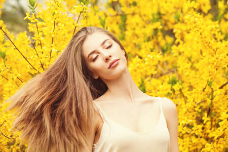 Cheerful woman with blowing hair outdoors