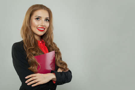 Successful woman holding red book and smiling on white background. Business and education concept