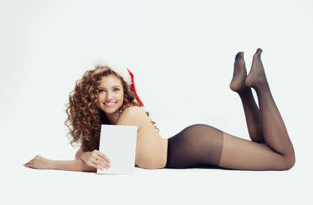 Donna felice in cappello di Babbo Natale che mostra carta banner di carta vuota con spazio di copia su sfondo bianco