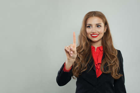 Happy businesswoman pointing her finger to empty copy space on gray banner background Stock Photo