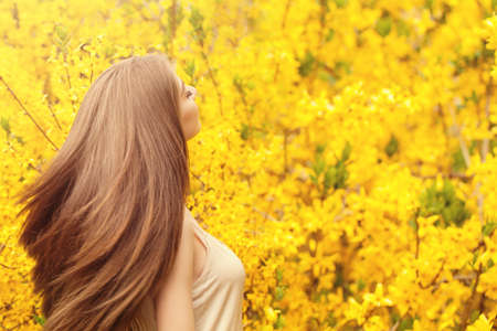 Romantic portrait of beautiful woman with long blowing hair on floral background