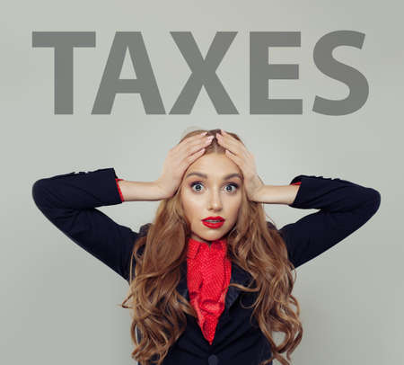 Stressed business woman with taxes inscription