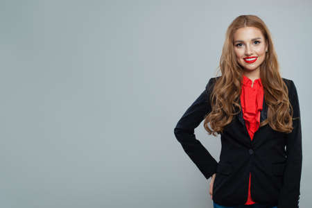 Happy woman student on gray background. Business woman in black suit portrait