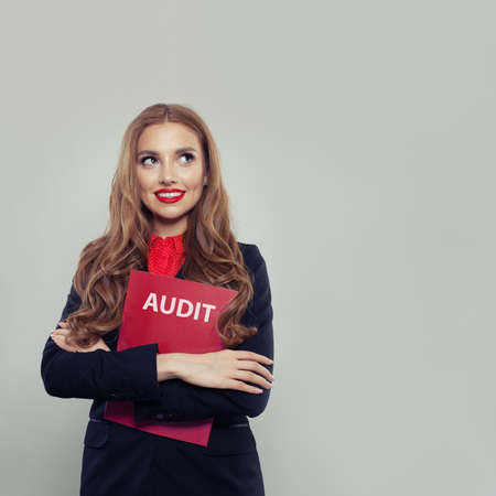 Happy business woman with audit report on gray background with copy space