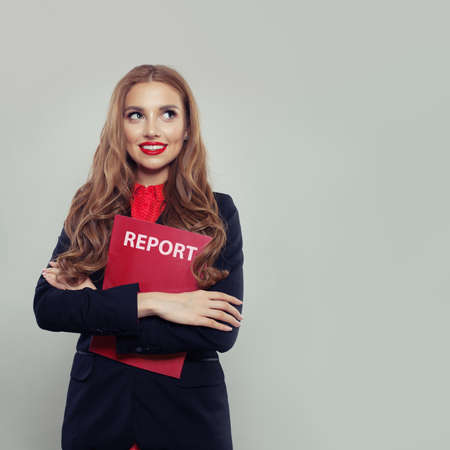 Happy business woman holding business report against white wall background