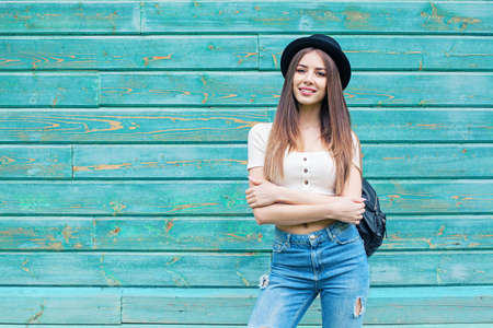 Happy young woman in blue denim on wooden background outdoors Stock Photo