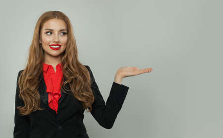 Business woman showing empty open hand on white background. Woman smiling, business and education concept