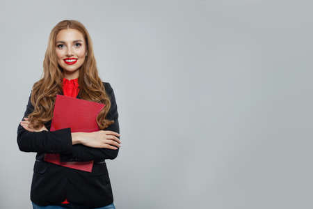 Happy business woman standing against white wall background. Businesswoman in black suit portrait Stock Photo