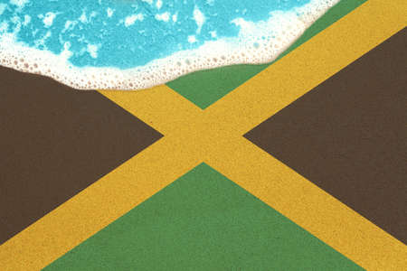 Sea wave on the sunny sandy beach with flag Jamaica. View from top on surf.