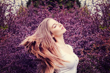 Young woman with long straight hair on flowers background