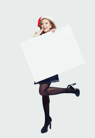 Surprised woman in black tights, high heels shoes and Santa hat holding empty paper banner card and standing on white background